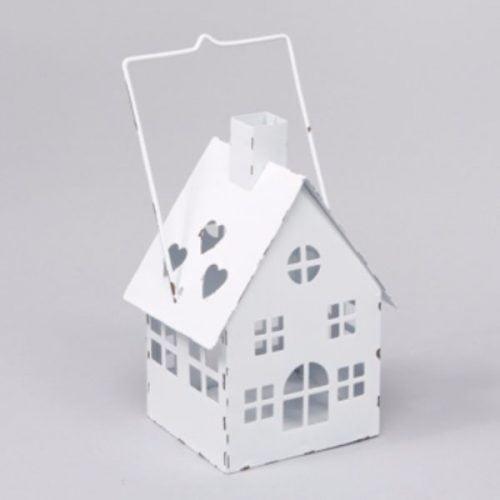 Ljuslykta för värmeljus i form av ett hus i vitmålad metall. Mått 8,5x8x15 cm (lxdxh, höjd till skorsten. Höjd till handtag 19 cm).