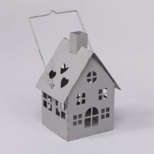 Ljuslykta för värmeljus i form av ett hus i gråmålad metall. Mått 8,5x8x15 cm (lxdxh, höjd till skorsten. Höjd till handtag 19 cm).