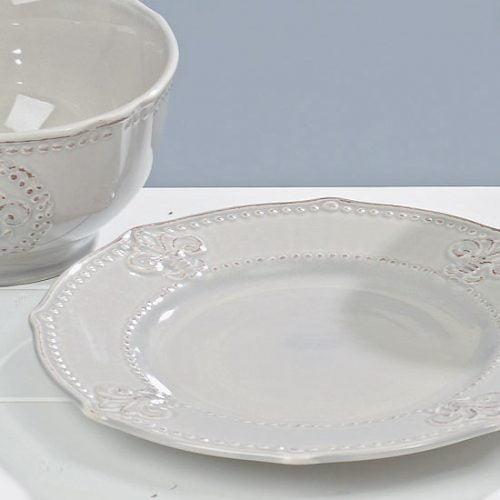 Assiett i grå keramik med dekor av fransk lilja, diameter 21 cm.