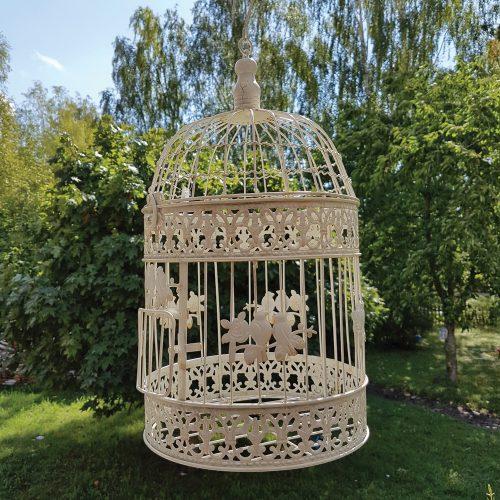 Rund fågelbur i gräddvit metall för dekoration. Fin till krukväxt, ljusslinga eller dekorativ som den är. Kan placeras ståendes eller hängas i kroken. Diameter 25 cm, höjd 44 cm.
