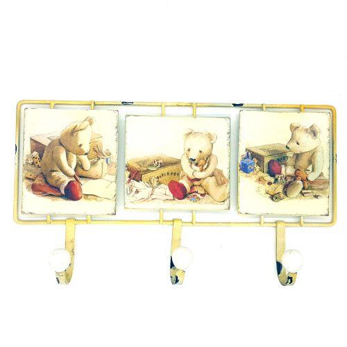 Hängare i metall med dekor av söta teddybjörnar och med porslinsknoppar på krokarna. En fin hängare till barnrummet. Mått 42,5x23,5 cm (lxh).